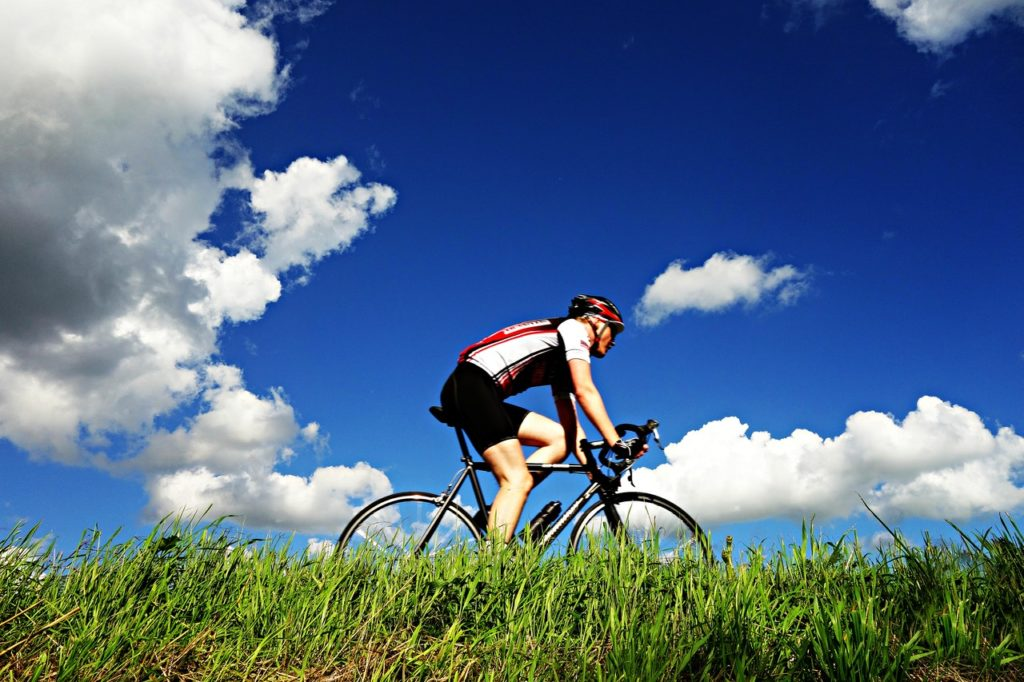 Healthy Cyclist after chiro visit, green grass & blue skies